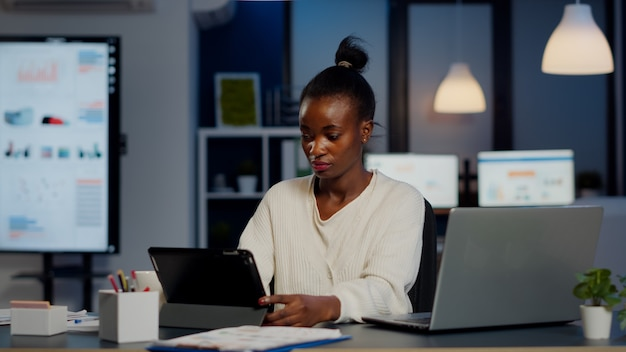 African manager woman using laptop and tablet in same time working overtime in business start-up office. busy multitasking busy employee analysing financial statistics overworking writing, searching.