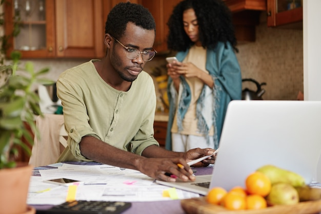 African married couple facing financial troubles. serious man in glasses calculating domestic expenses using laptop computer, sitting at kitchen table with lots of papers. family budget and debts