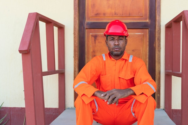 Африканский механический человек сидит в перерыве. понятие инженера или техника.