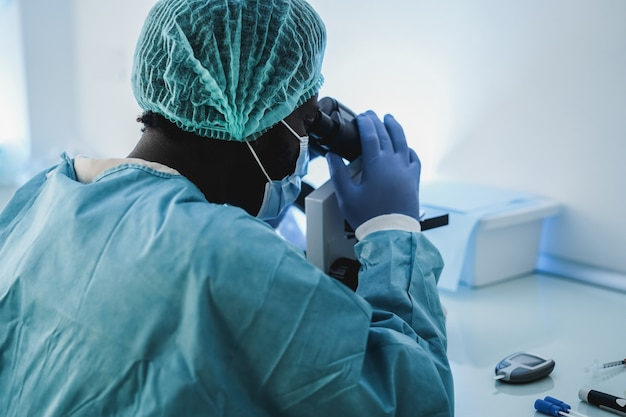 African medical worker in hazmat suit working with microscope inside lab hospital during coronavirus outbreak