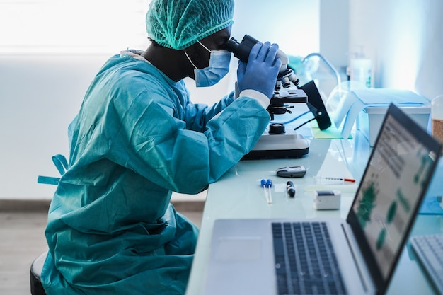 African medical worker in hazmat suit working with microscope inside laboratory hospital during coronavirus outbreak - focus on hand