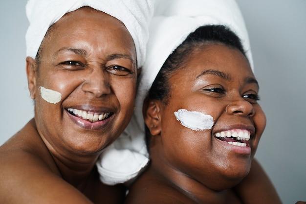 Африканские мать и дочь делают косметические процедуры дома с помощью маски для кожи - уход за телом и концепция семьи - сосредоточение внимания на рте девушки