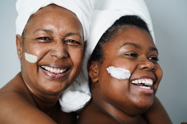 African mother and daughter doing beauty treatment at home using skin mask - body care and family concept - focus on girl mouth