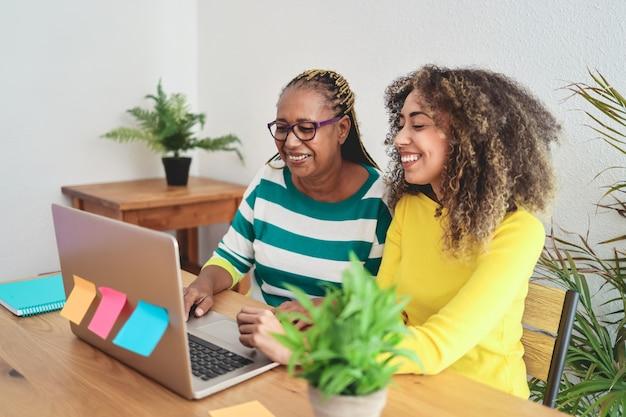 Африканская мать-дочь с удовольствием использует портативный компьютер дома