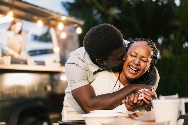 African mother and son having fun together outdoor at food truck restaurant - love and family lifestyle concept - focus on mum face
