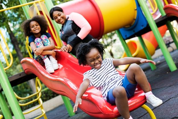 彼女の2人の子供たちと公園で楽しいアフリカの母親