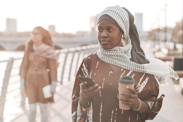 아프리카 이슬람 여성이 도시를 산책하는 동안 커피를 마시고 휴대전화를 사용합니다.