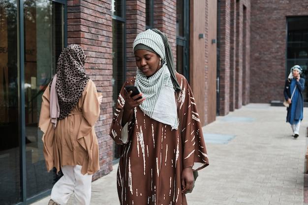 전통 의상을 입은 아프리카 이슬람 여성이 휴대전화로 메시지를 읽고 도시를 산책하는 동안 웃고 있다