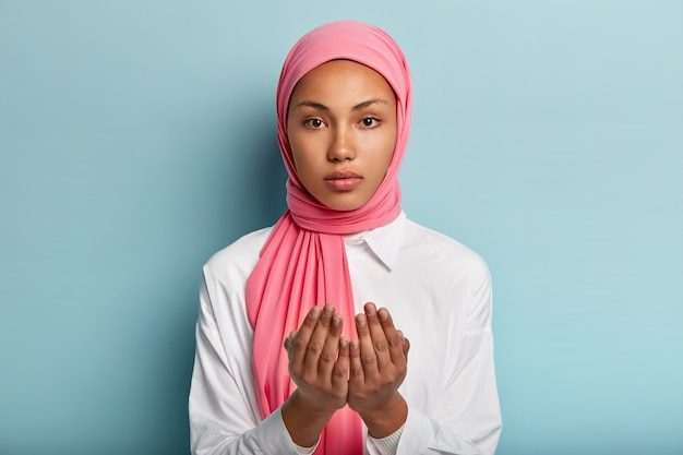 African muslim woman makes traditional prayer to god, keeps hands in praying gesture