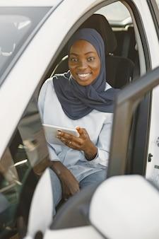 Donna musulmana africana seduta nella sua auto e con in mano una tavoletta digitale. lavorare da remoto o condividere informazioni. tecnologie nella nostra vita.