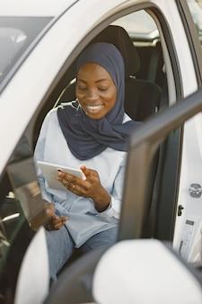 Donna musulmana africana seduta nella sua auto e con in mano una tavoletta digitale. lavorare da remoto o condividere informazioni.