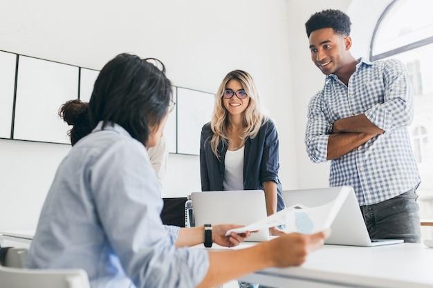 腕を組んで立って、アジアのマネージャーを見ている市松模様のシャツを着たアフリカのサラリーマン。何かについて話し合ったり、ラップトップを使用したりするフリーランスのweb開発者の屋内ポートレート。