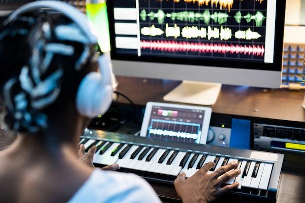 Молодой человек из африки или смешанной расы трогает клавиши фортепианной клавиатуры, сидя перед экраном компьютера и сочиняя музыку