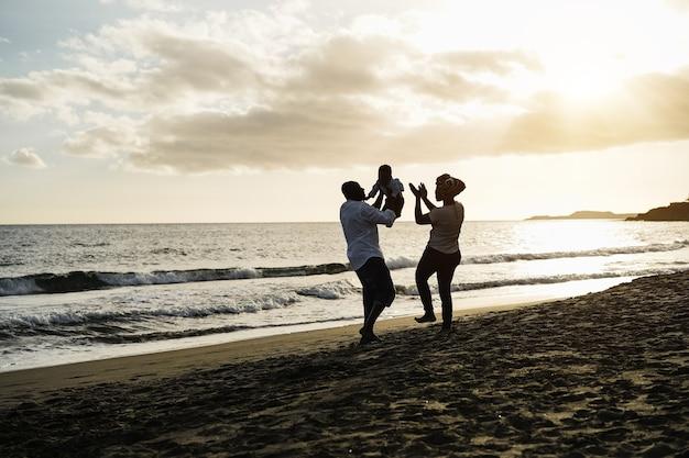 日没時にビーチで楽しんでいるアフリカの両親と幼い息子-シルエットに焦点を当てる