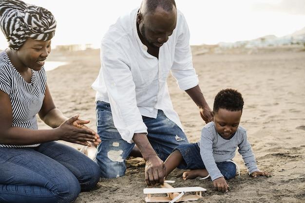 ビーチで木製飛行機を楽しんでいるアフリカの両親と幼い息子-小さな男の子の顔に焦点を当てる