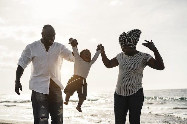 African parents and little son having fun on the beach at sunset - family people and love concept
