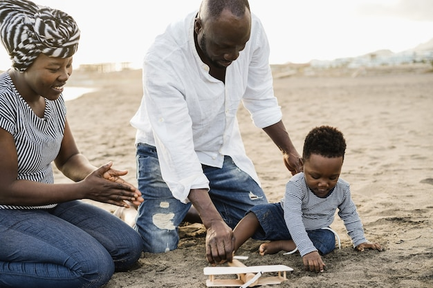African parents and little son having fun with wood airplane on the beach - focus on little boy face
