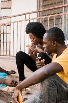 階段で食べるアフリカの人々