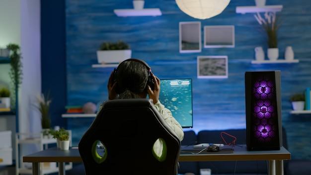Rgbキーワードを使用してオンラインスペースシューティングビデオゲームをプレイするヘッドセットでゲーミングチェアに座っているアフリカのプレーヤー。強力なパソコンを使用したプロサイバーストリーミングオンラインビデオゲームの新しいグラフィック