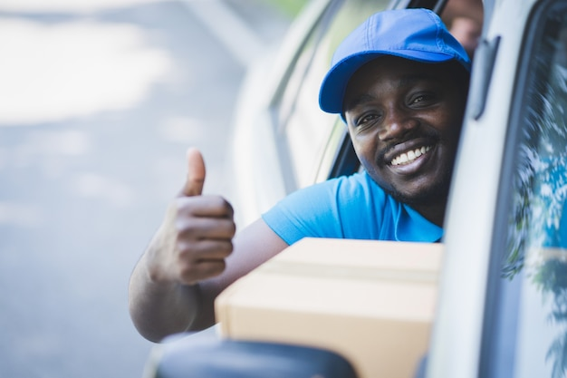 車でパッケージを配達するアフリカの郵便配達宅配便の男
