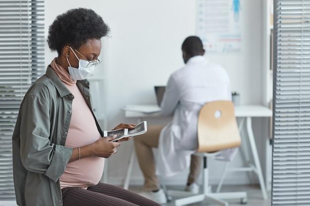보호용 마스크를 쓴 아프리카 임산부가 병원을 방문하는 동안 손에 든 초음파 이미지를 보고 앉아 있다