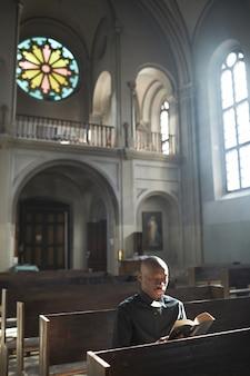 教会のベンチに座って聖書を読んで祈っているアフリカの司祭