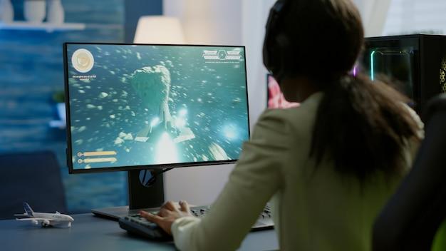 サイバーゲームトーナメントの競争力のあるビデオゲームでヘッドセットをプレイしているアフリカのプロeスポーツゲーマー。サイバースペースでの仮想選手権、rgb強力なパーソナルコンピューターで実行するeスポーツプレーヤー