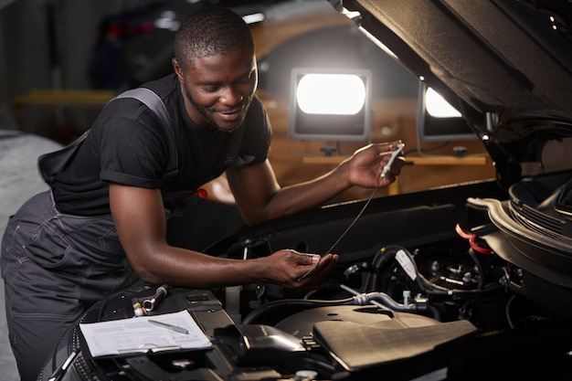 African professional auto service technician in uniform standing near car hood