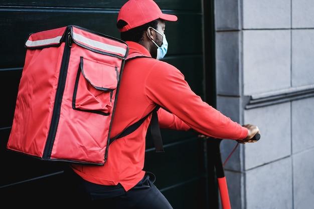 Африканский всадник доставляет еду на электросамокате - в центре внимания рюкзак