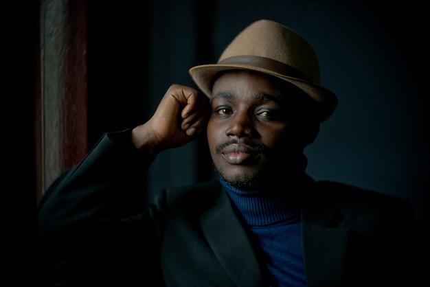Африканский грустный человек, сидящий в темной комнате, сдержанный стиль