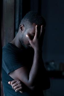 Африканский грустный человек, стоящий в темной комнате, сдержанный стиль
