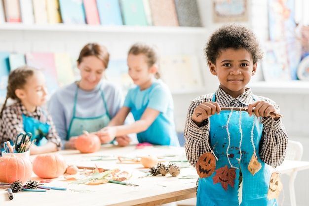 African schoolboy in blue apron holding stick with halloween decorations made up of dry leaves hanging on threads
