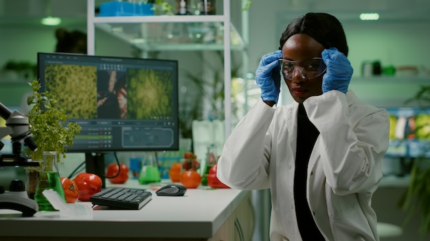 African scientific woman putting her medical glasses looking at camera