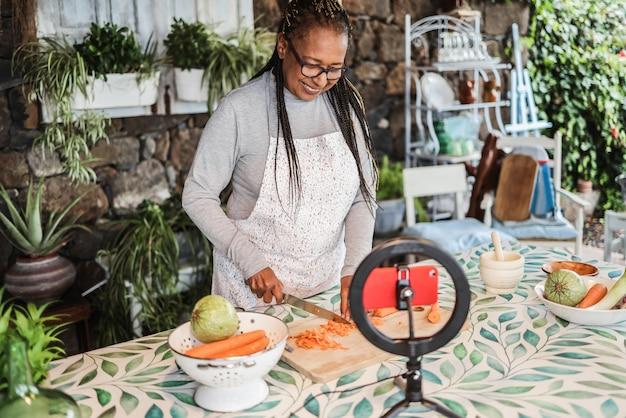自宅でウェビナーマスタークラスのレッスンのためにオンラインでストリーミングしながら屋外で料理をするアフリカの年配の女性-食べ物とインフルエンサーの概念-顔に焦点を当てる