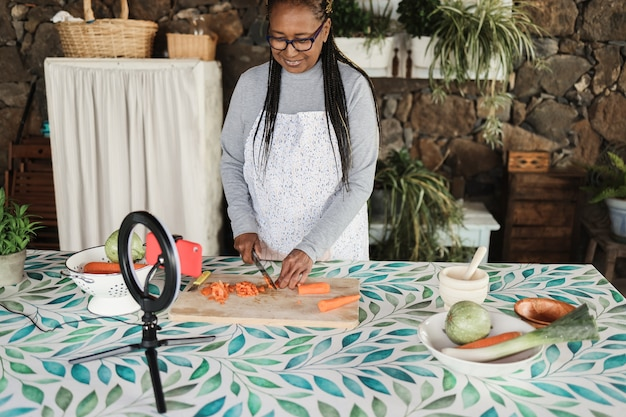 African senior woman cooking outdoor while streaming online for webinar masterclass lesson at home - food and influencer concept - focus on face