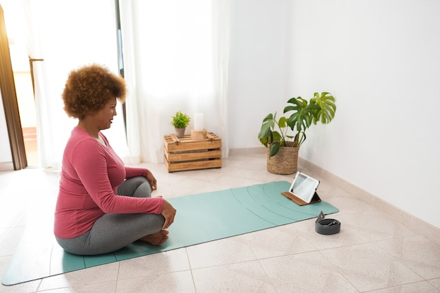 African senior woman doing online yoga class at home - focus on face