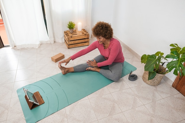 African senior woman doing online yoga class at home