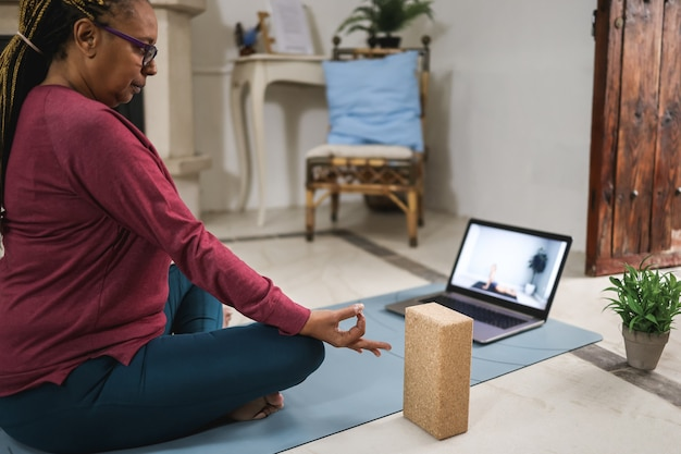 African senior woman doing online yoga lesson at home - focus on hand