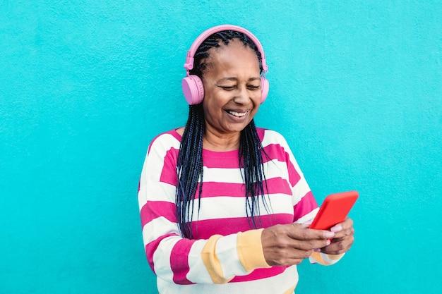Африканская старшая женщина, слушающая музыку в приложении для мобильного телефона - сосредоточьтесь на лице