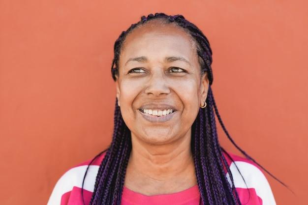 빨간색 배경으로 웃는 아프리카 수석 여자