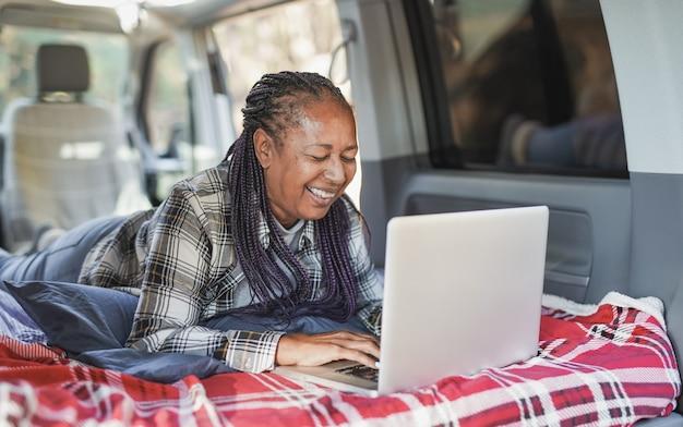 ミニバンキャンピングカー内でコンピューターのラップトップを使用してアフリカの年配の女性