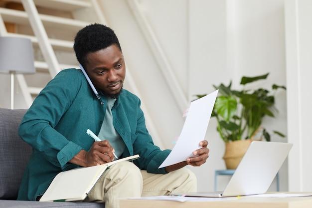 ノートパソコンの前のソファに座って、自宅でオンラインで作業している事務処理をしているアフリカの真面目なビジネスマン