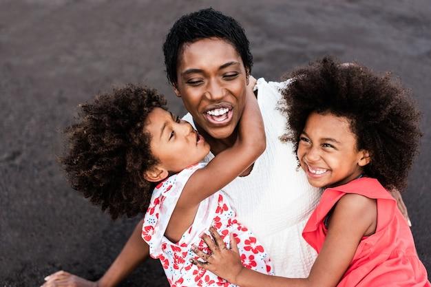 夏休みの日没時にビーチで遊ぶアフリカの姉妹の双子と母親-女の子の顔に主な焦点