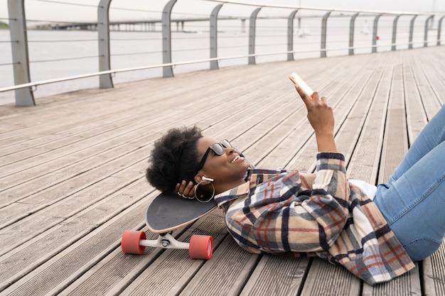 스케이트 공원에서 스케이트보드에 누워 스마트폰 흑인 여성 메시징에서 아프리카 스케이팅 소녀 채팅