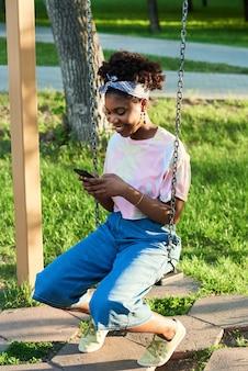 ブランコに座って、屋外で携帯電話を使用してアフリカの笑顔の女性