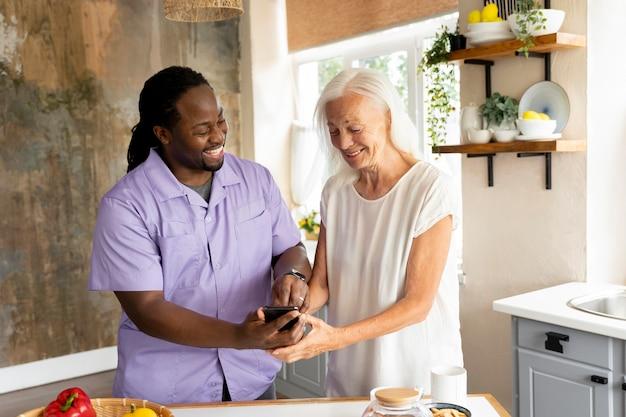 Африканский социальный работник помогает пожилой женщине
