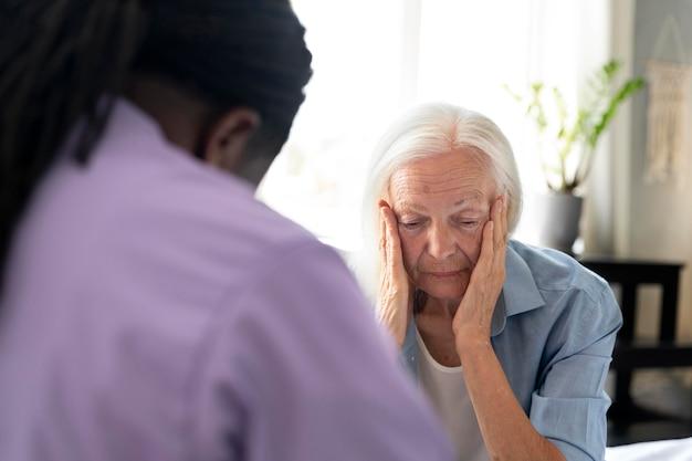 Африканский социальный работник заботится о пожилой женщине