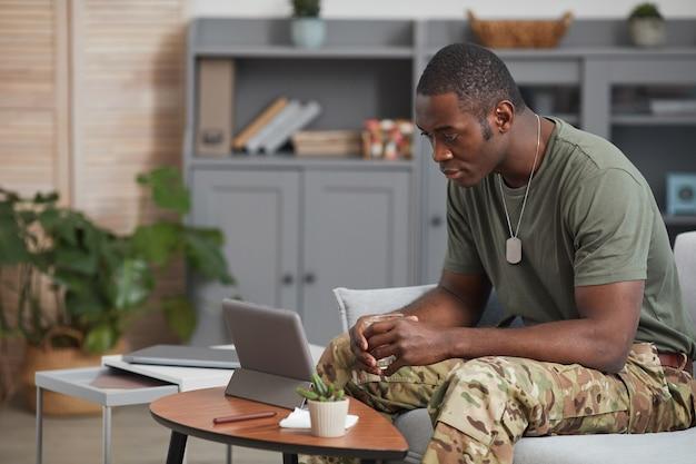아프리카 군인 디지털 태블릿 앞에 소파에 앉아 온라인으로 이야기
