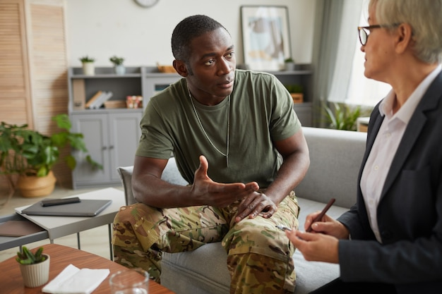 African soldier talking to therapist while they sitting on sofa during therapy at office