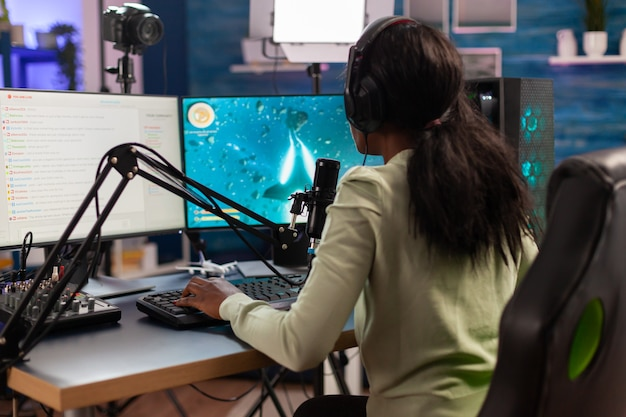 아프리카 우주 사수 e-스포츠 선수가 마이크에 대고 말하는 친구들과 라이브 게임을 하고 있습니다. 온라인 챔피언십을 위해 헤드폰과 키보드를 사용하여 재미를 위해 바이러스성 비디오 게임을 스트리밍합니다.